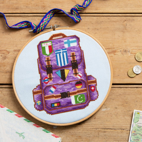 Cross stitch of a purple hiking backpack covered in flag patches from many countries