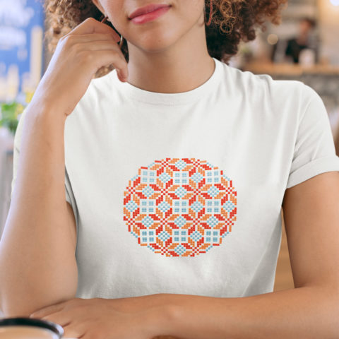 Geometric tatreez pattern stitched in a circle on a white t-shirt in red and blue